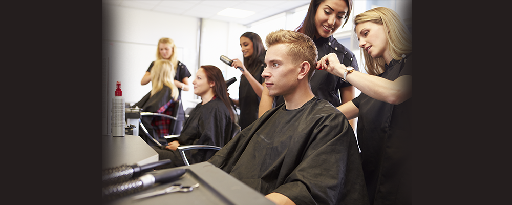 Students work on customers in a beauty salon while an instructor provides guidance.