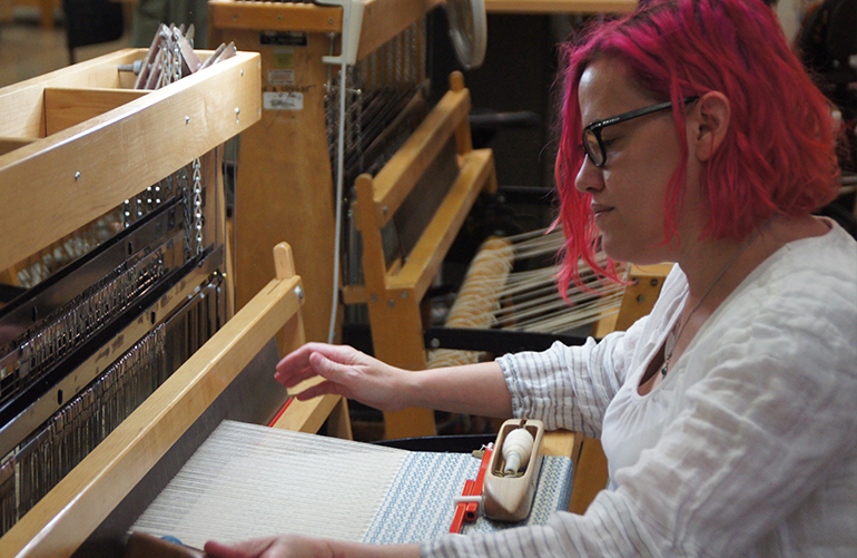 A student sits at a weaving loom working the shuttle back and forth creating fabric.